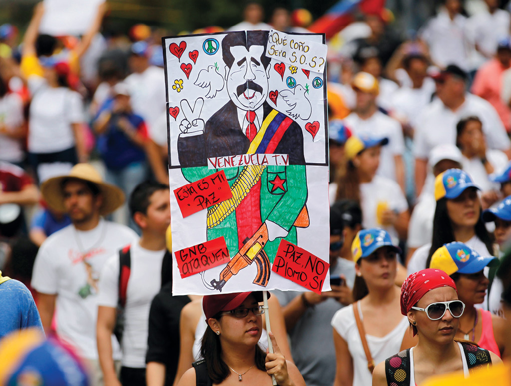 "An antigovernment protester holds a poster with a caricature of Venezuela's President Nicolas Maduro 2 March 2014 during a rally against his government in Caracas. The poster reads, ""What the hell does SOS mean?,"" ""Peace no, bullets yes."" Subsequently, thousands of antigovernment demonstrators marched in the capital trying to keep up the momentum during months of protests demanding Maduro's resignation. (Photo by Jorge Silva, Reuters)"