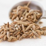 cumin seeds spilling from a measuring spoon