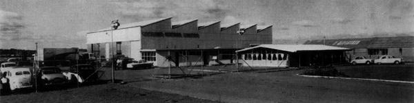 This photo shows British Leyland's New Zealand truck assembly plant on Carbine Road in Mt Wellington, Auckland. Assembly took place in the main building with the saw-tooth roof, while the small building to the left served as the BLMCNZ head-quarters and the single-storey building in the foreground housed the Accounts and Service Office. The site was redeveloped in 1974/75 to become NZMC's P&A or Unipart division. Thanks to former NZMC employee Stewart Park for identifying this photo.