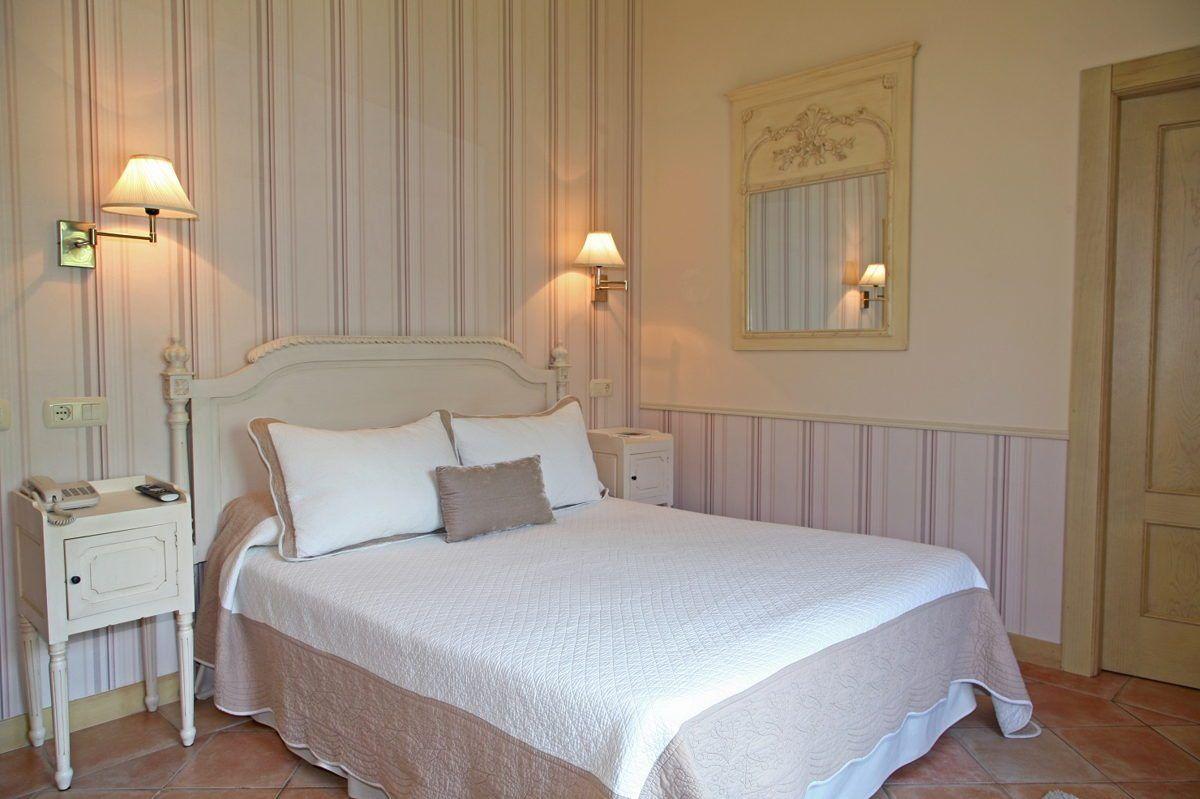 Habitación con bonito papel pintado en tonos morados con cama matrimonial y vistas a la Sierra del Cuera en Hotel Rural Arpa de Hierba Llanes