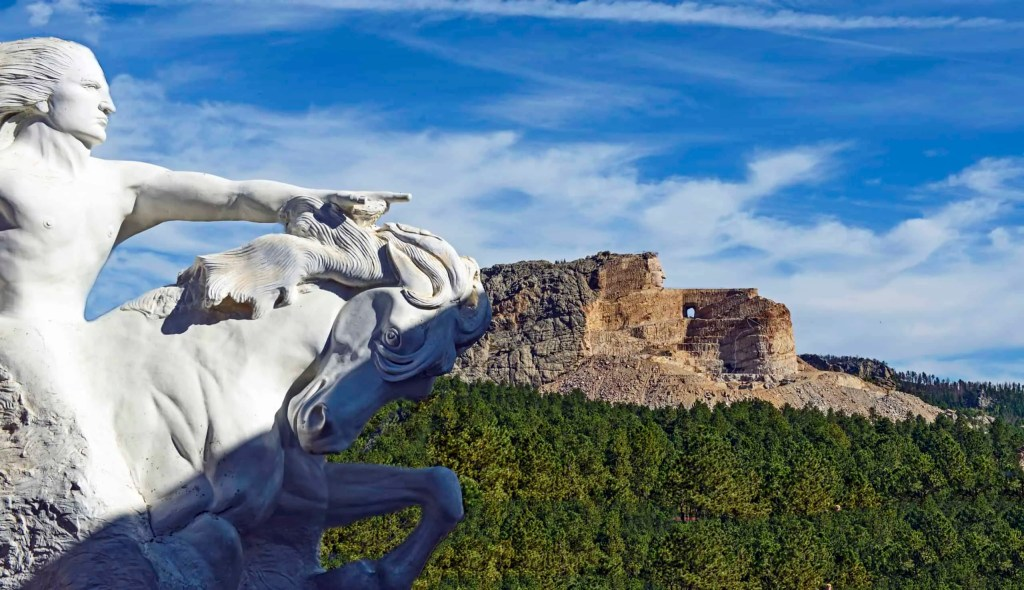 Model of the Crazy Horse Memorial and the carved mountain