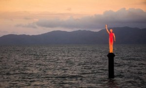 red sculpture of woman stands on plinth above the ocean