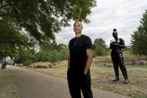 Artist Thomas J Price stands in front of statue of Black woman
