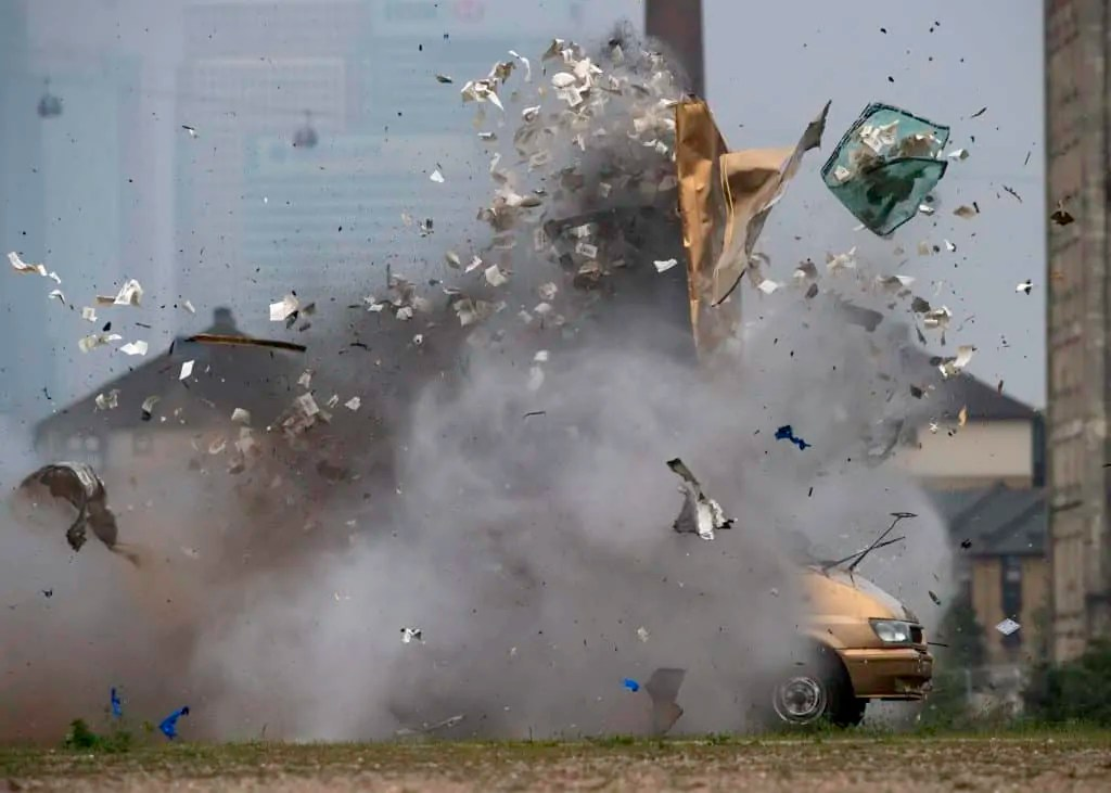 A gold van is blown up sending bank notes into the air with Canary Wharf in the background Art World Roundup