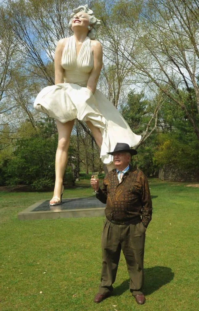 A man wearing a brown outfit and hate holds a glass of champagne in front of a 26-foot-tall statue of Marilyn Monroe