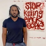 """Artist Rashid Johnson stands beside his painting for """"Show Me the Signs"""""""