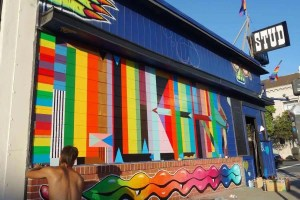 Man paints a colourful mural on the outside of a San Francisco bar