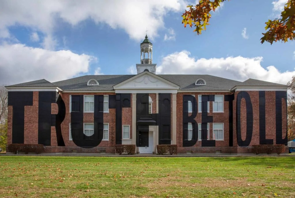 "New York building covered in large black letters reading ""Truth Be Told"" by artist Nick Cave. art World Roundup"