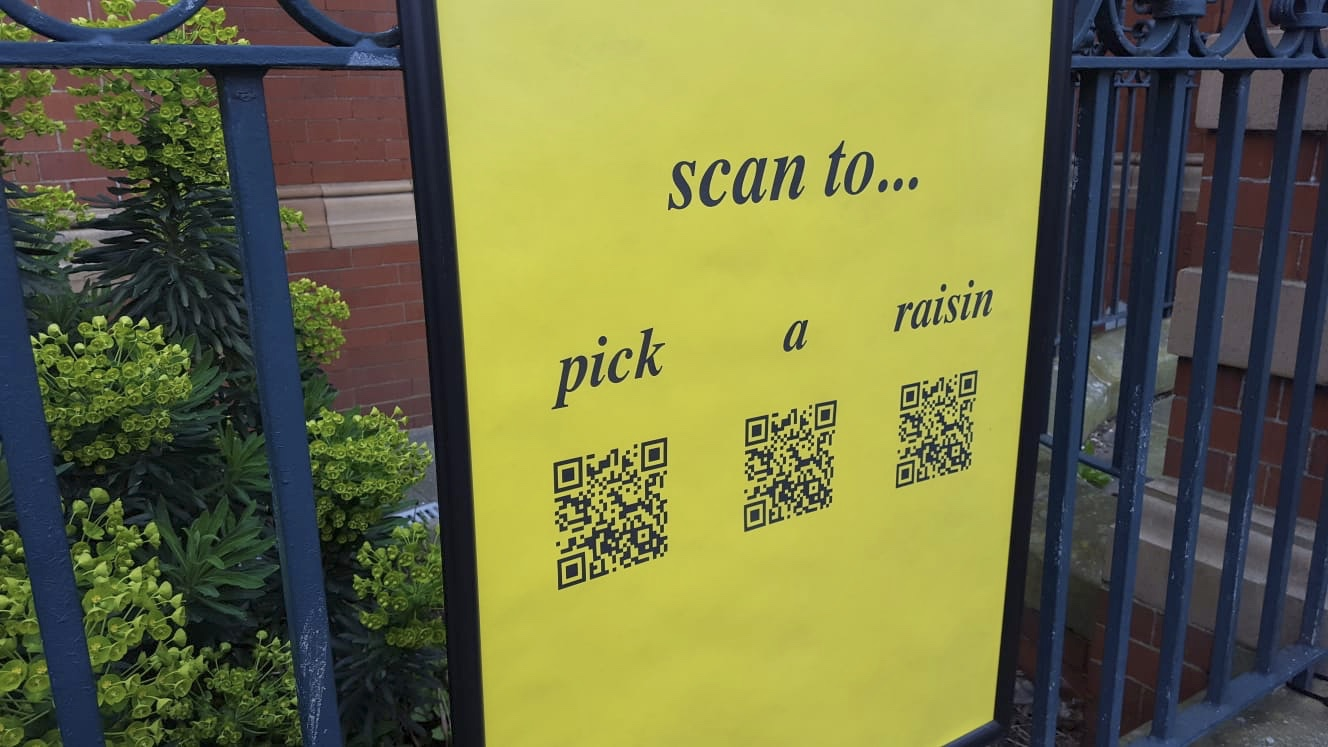 close up photograph of yellow poster on railings with text that reads:
