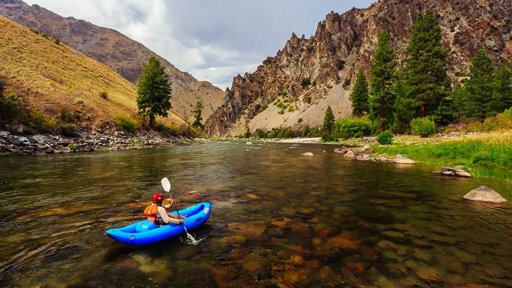 An inflatable kayak floats along a calm stretch while whitewater rafting on the Middle Fork Salmon River in Idaho with ARTA river trips