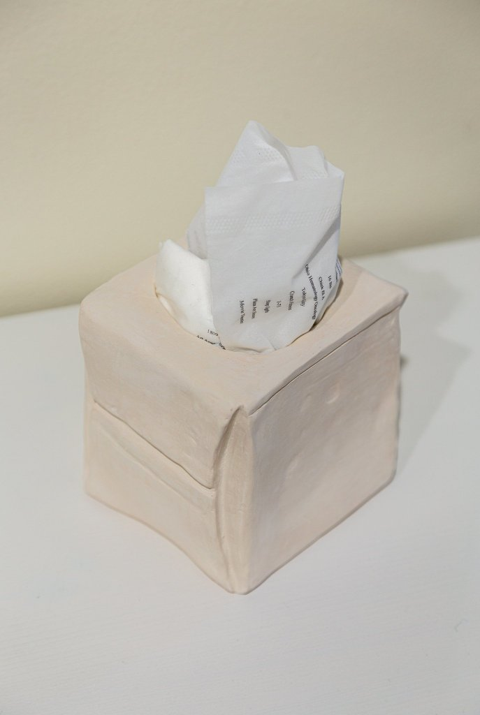 A photo of Krista Sheneman work. A ceramic tissue box. The tissue coming out of the box with different places listed on the tissue.