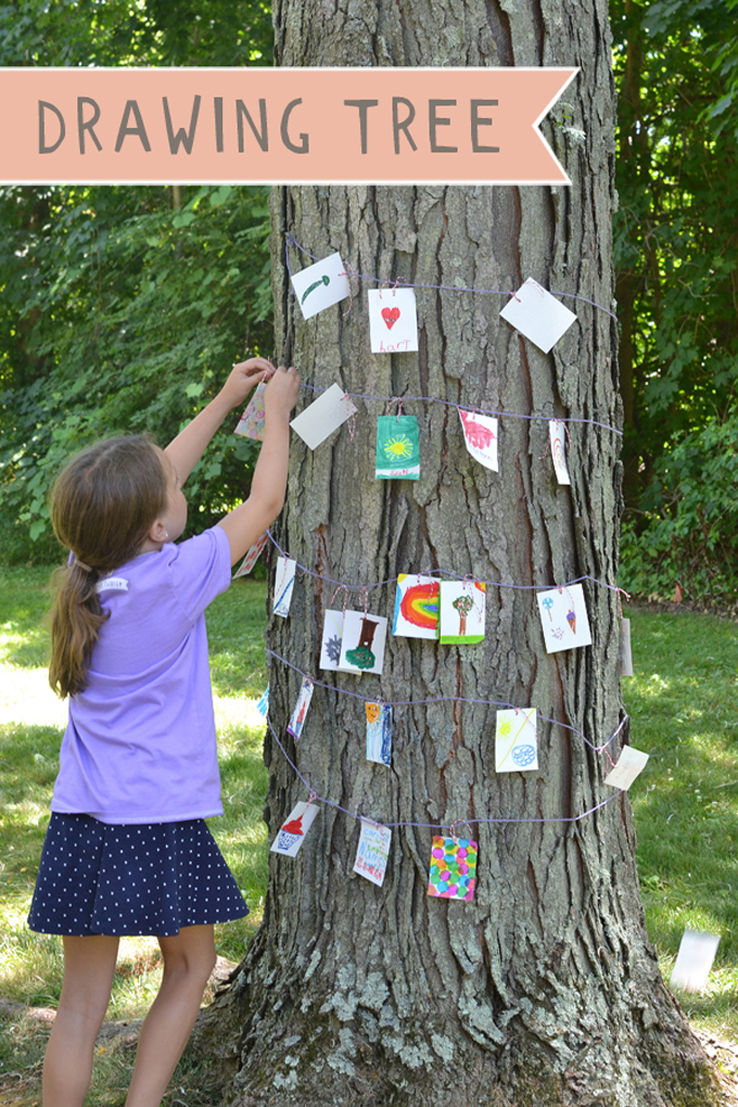 Kids use drawing prompts to create little drawings that they hang on a tree.