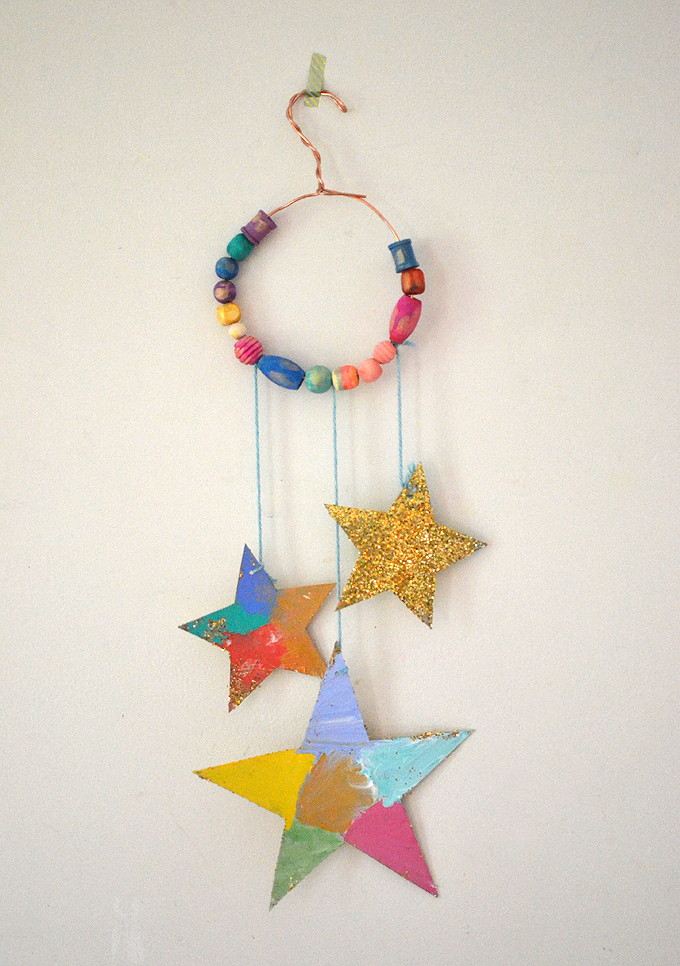 Kids make glittery star mobiles with cardboard, wire, and painted wooden beads.