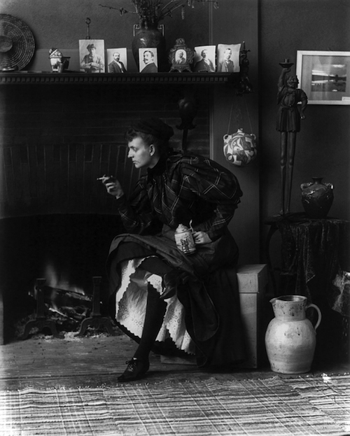 Frances_Benjamin_Johnston,_full-length_portrait,_seated_in_front_of_fireplace,_1896
