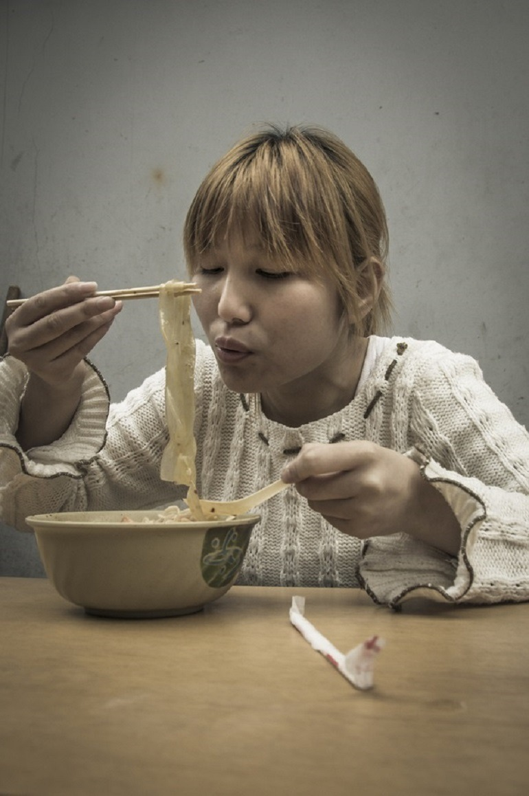 Image- A woman in a white sweater eats noodles in this street photography by Ron Gessel, take on 'The Streets of Shanghai'