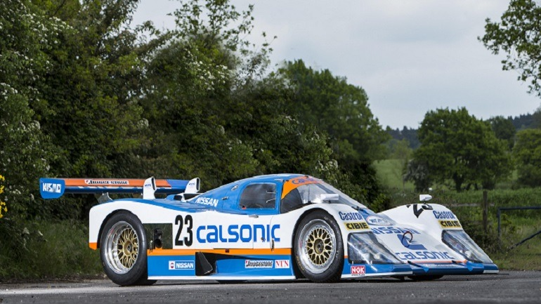 Image- The 1987 Nissan R87E Group C Sports Prototype has calsonic written on it. It is a beutiful racing care