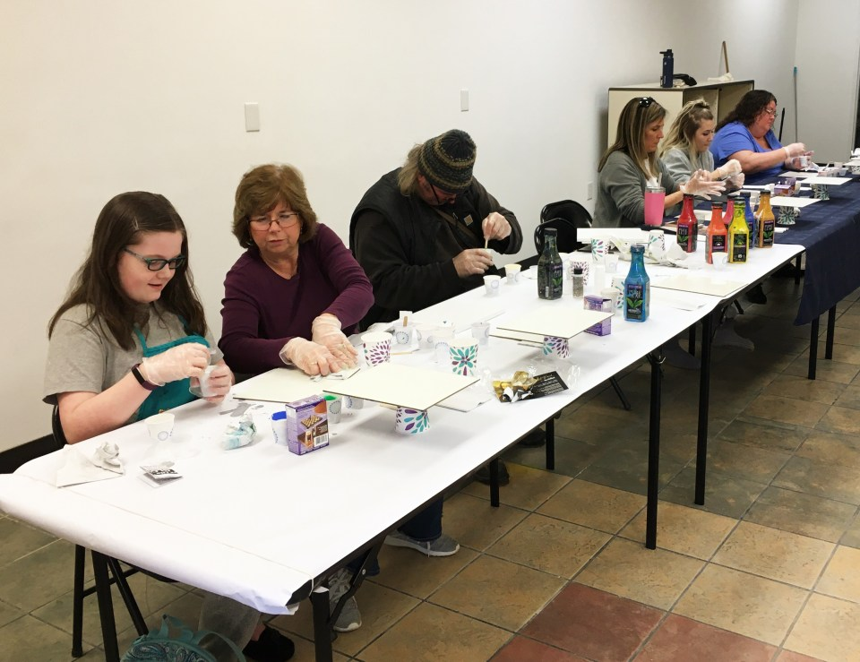 People in a paint-pouring class at an art supply store