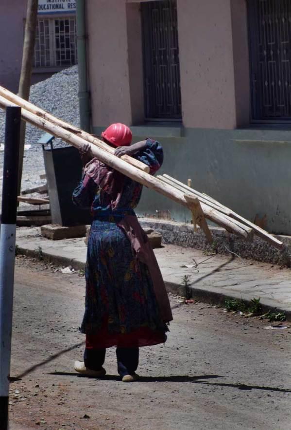 ethiopian woman wearing hardhat carries logs on her shoulder