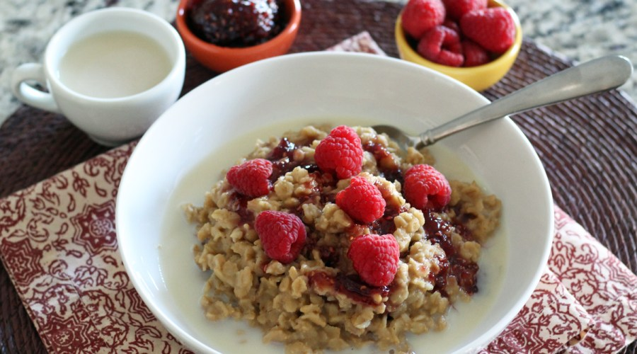 a large white bowl of the finished peanut butter oatmeal with almond milk pour around it, raspberry jam drizzled on, topped with fresh raspberries