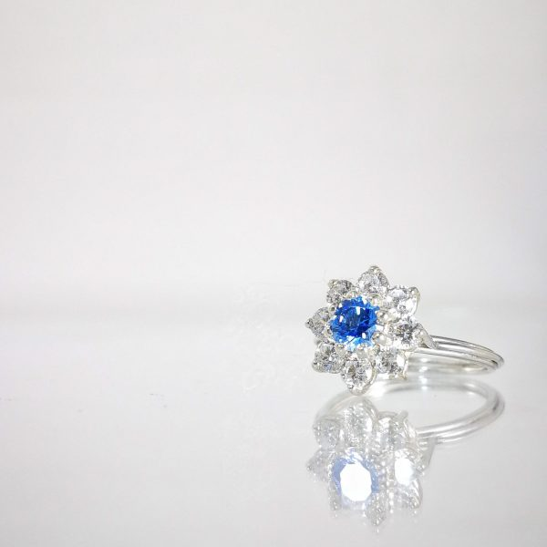 Silver wired ring, cluster setting with a blue center stone an zirconia all around