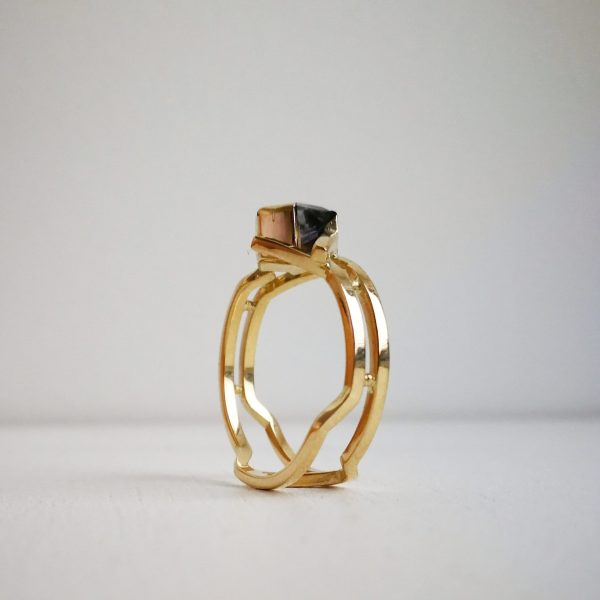 yellow gold ring, with an intricate shank made of two square wires. Central stone is an hexagonal cut iolite set in an open setting.