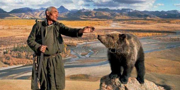 Dukha, a tribe of Mongolians, elder man reaching out to touch a wild bear, (http://hamidsardarphoto.com/).