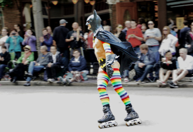 movie drinking games: Man on rollerskates wearing a Batman cape and cowl, and rainbow stripe stockings.