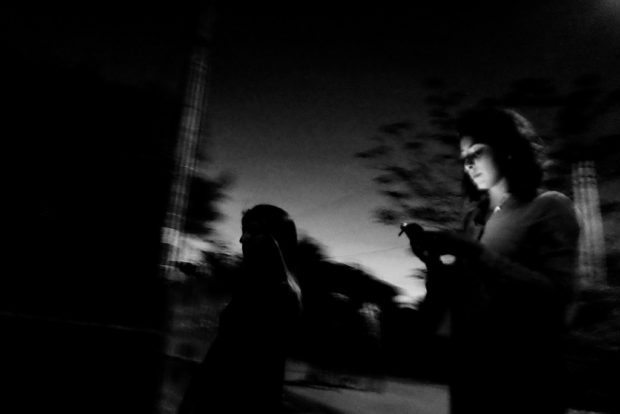 Technosexuality: Woman on cell phone at night, phone illuminates her face