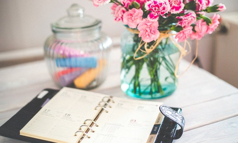 Flowers in a vase and a planner to make notes when organizng a stress-free move.