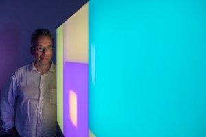 Il gallerista e curatore Paul Stolper con un Light painting di Brian Eno alla GalleriaMichelaRizzo alla Giudecca (Ve)