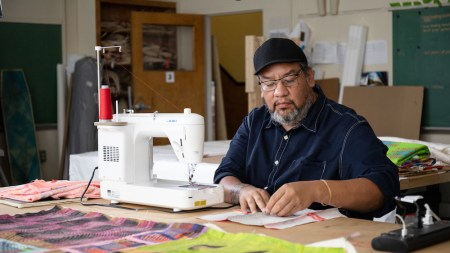 Jeffrey Gibson sewing in his studio.