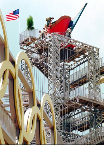Armajani's cauldron tower for the 1996 Olympics. Construction workers hoist a giant red cauldron a top a tower made of trusses.