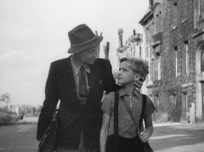 A man in a suit and a porkpie hat grips a towheaded boy by the neck and looks at him imploringly as they walk down a deserted street