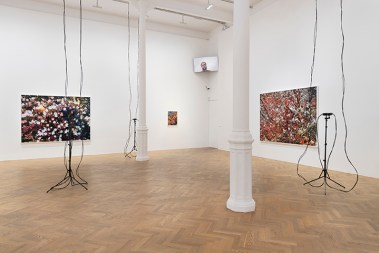 Cameras surveil a gallery with white walls and parquet flooring; high in a corner, a monitor shows a viewer looking at the exhibition from home.