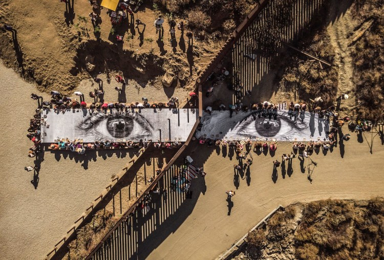 A JR project resembling a long photograph of eyes against an arid landscape intersected by a fence.