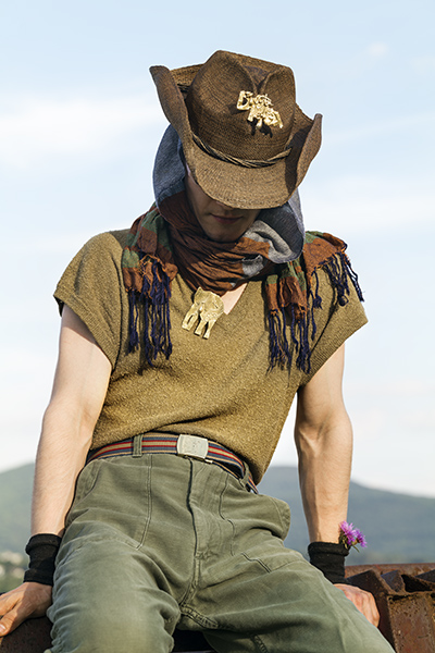 photo of a man in army green pants and top, camo scarf, and cowboy hat looking downward