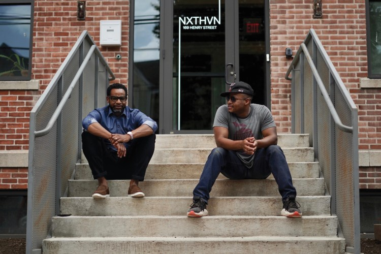 NXTHVN founders Jason Price, left, and Titus Kaphar seated on the steps at the entrance of NXTHVN.