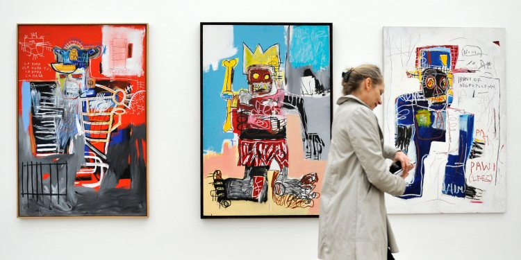 """A woman passes by the artworks of Jean-Michel Basquiat titled """"La Hara"""" (1981, acrylic and oilstick on wood), """"Untitled"""" (1982, acrylic, oilstick and spray paint on wood) an """"Irony of Negro Policeman"""" (1981, acrylic, oilstick and spray paint on wood), from left, in the Fondation Beyeler in Riehen, Switzerland, Friday, May 7, 2010. The exhibition with the artwork of American artist Jean-Michel Basquiat (1960-1988) can be seen from May 9 until Sept. 5, 2010. (AP Photo/Keystone/Georgios Kefalas)"""