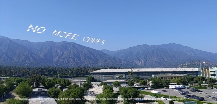 "An AR rendering of ""NO MORE CAMPS"" over Santa Anita Assembly Center in California by curator and writer Karen Ishizuka / Tsuru For Solidarity."