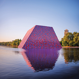 A digital rendering of a trapezoidal blue and red structure seems to emerge from the water