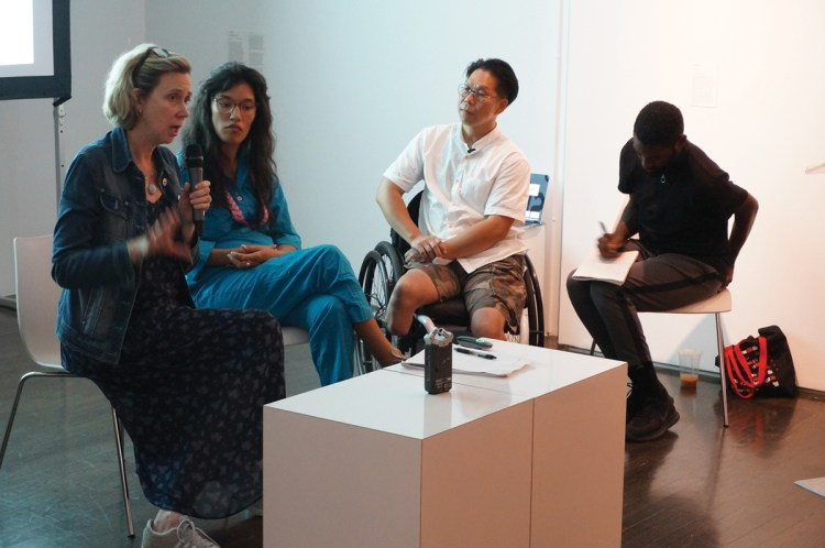 From left, curator Catherine Morris, artist Pelenakeke Brown, and dancers Donald Lee and Jerron Herman at the event Access Check: Mapping Accessibility 2.0, 2019, at The 8th Floor. The participants are seated in front of a low white table, as Morris holds a microphone.