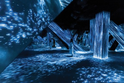 Lines of cool blue light dance across the floor and the sides of slanted columns in an interactive installation