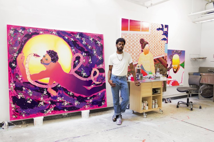 Devan Shimoyama in front of two vibrant works in progress in his Pittsburgh studio, located on the Carnegie Mellon University campus.