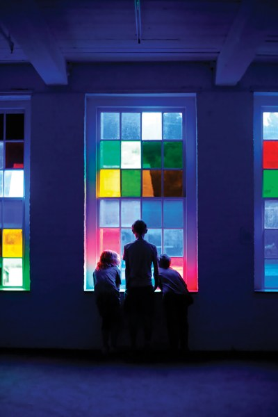 Kids gaze through multicolored glass windows in the 2019 MASS MoCA exhibition 'We Already Have What We Need' by Cauleen Smith.