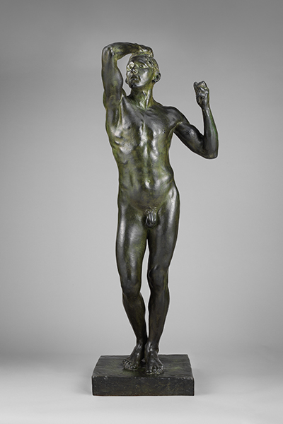 Bronze sculpture of a nude young man with one hand on his head by Auguste Rodin