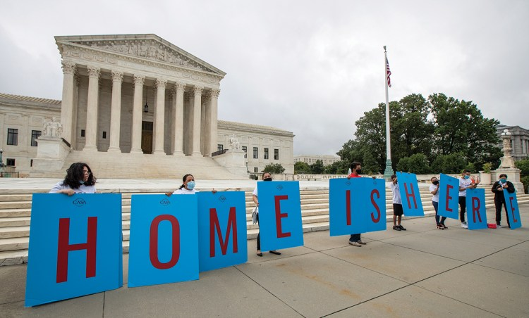 """Protestors hold up blue signs with red text that spell out """"home is here."""""""