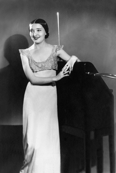 A grayscale photo of a white woman with a center part and a bun posing with a theremin.