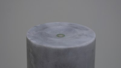 close up of the top of a cylindrical gray column with a single contact lens resting on top