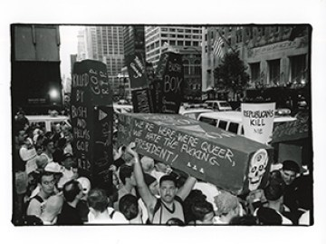 AIDS activists hold up coffins with slogans written on them in a protest