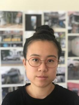 Met dank aan de kunstenaar. Een foto van de kunstenares Anne Wu. Ze draagt een roodomrande bril met haar haar in een knot. Op de enigszins onscherpe achtergrond hangen foto's en afbeeldingen aan de muur.